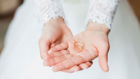 bride holds wedding bands