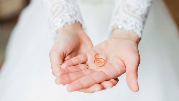bride holds wedding bands