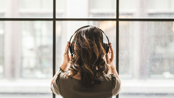 a woman listening to music and watching the window