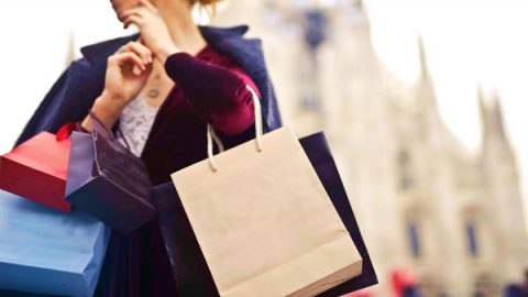 a woman is holding many shopping bags