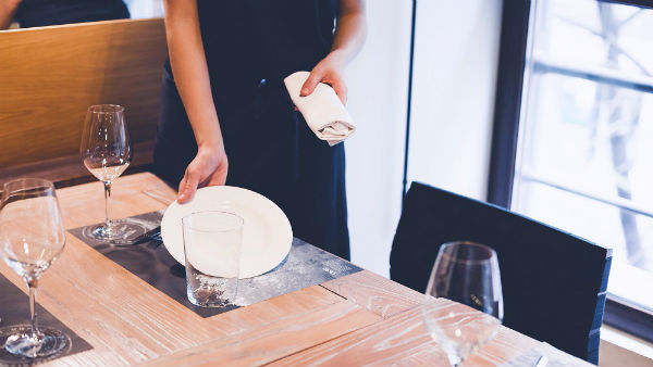 a waitress putting plate on table