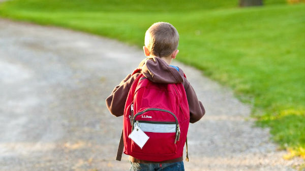 a boy carrying a heavy backpacks
