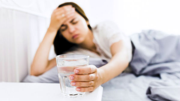 woman feels sick taking glass of water
