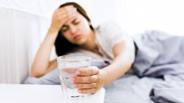 woman feels sick taking glass of water