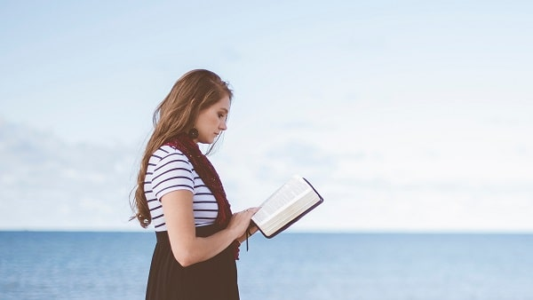 girl at the seaside reading book