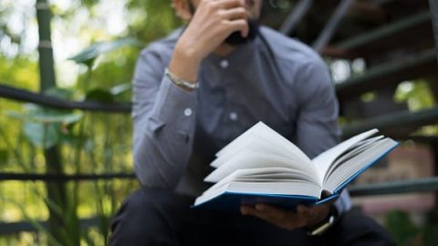 a man looking at a book thinking