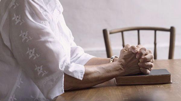 hand praying on bible book