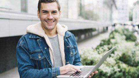 Modern man using laptop in urban environment