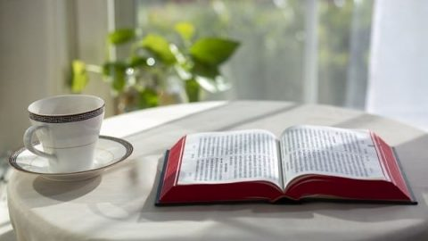 The bible book and the coffee mug on the table