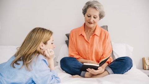 Daughter and mother reading in bed