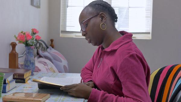 Woman in purple blouse is reading