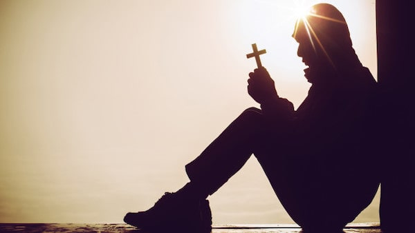 Silhouette man holding a cross in prayer
