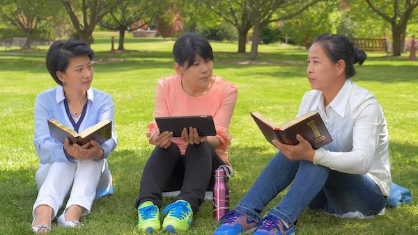 Three people sitting on the grass reading a book