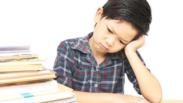 boy is unhappy doing homework
